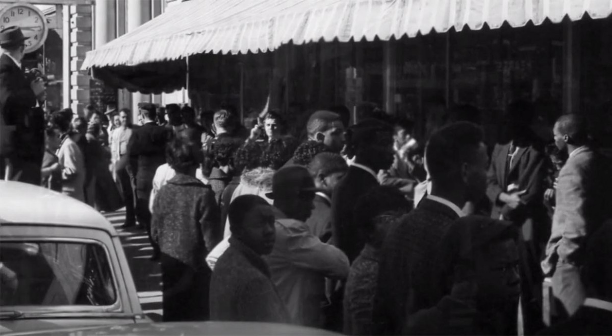 crowd standing in front of store with lunch counter