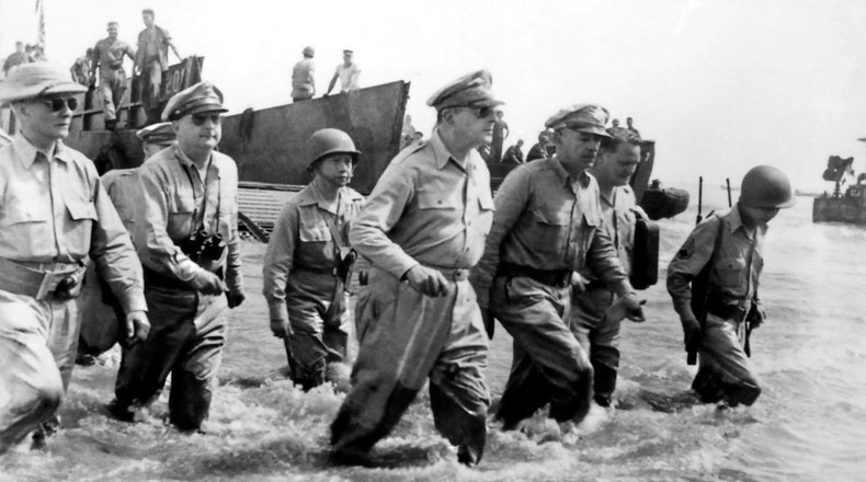 Gen. Douglas MacArthur wades ashore during initial landings at Leyte, Philippine Islands.
