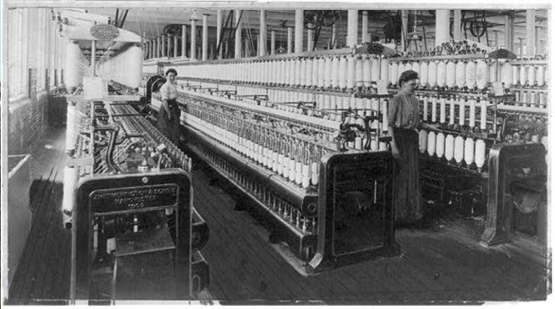Textile factory with two women at machines, ca. 1910. Credits: Photo courtesy of the Library of Congress.