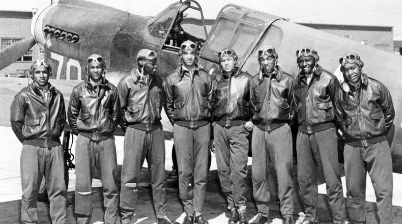 Eight Tuskegee Airmen in front of a P-40 fighter aircraft.
