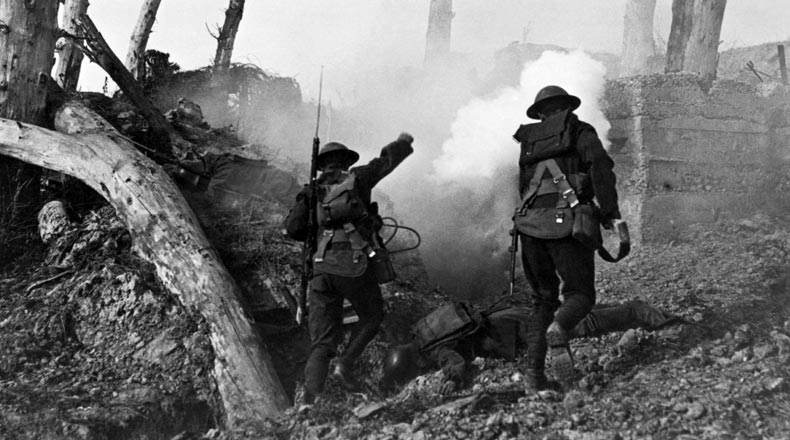 Two United States soldiers run past the remains of two German soldiers toward a bunker.